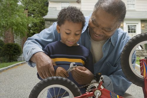 Older man helping young boy repair a bike