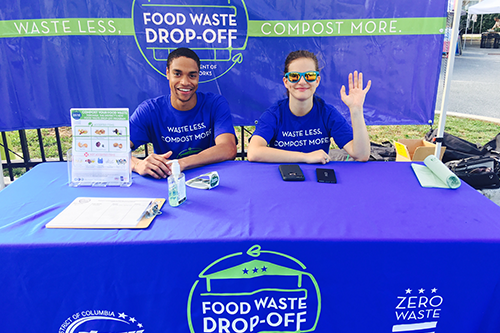 Young man and women working a booth for Food Waste Drop-Off