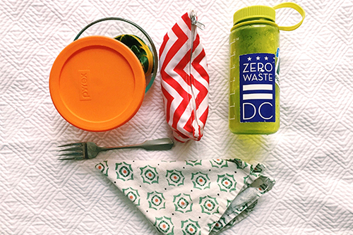 Reusable lunch featuring reusable fork, cloth napkin, reusable water bottle, and lunch box